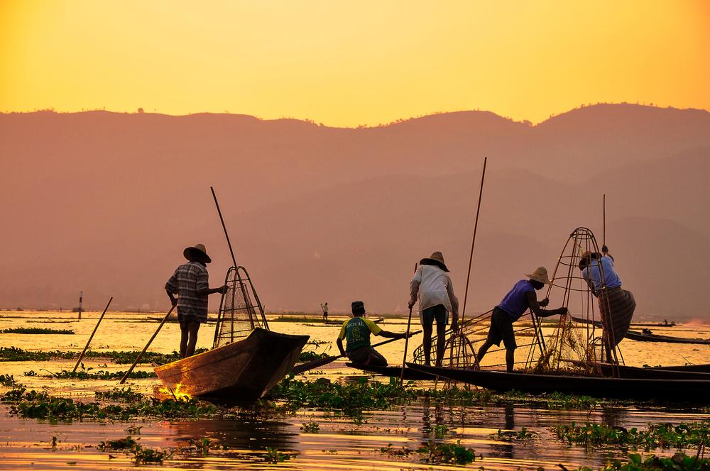 Pescadores al atardecer en un lago de Asia