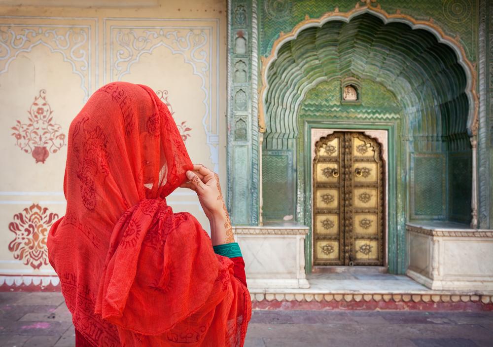 Mujer con un pañuelo rojo mirando una de la puertas del Palacio en Jaipur