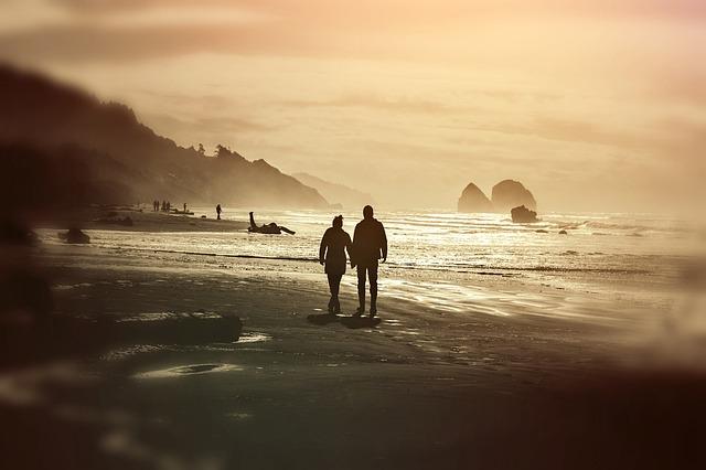 Pareja caminando por la playa al atardecer